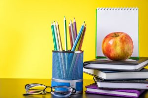 Back to school concept. School supplies and books on yellow background. Place for text.