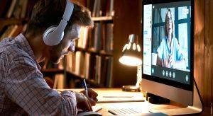 Male student wearing headphones video conference calling watching webinar.