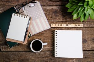 New year resolutions or goals list. Office desk table with notebooks, coffee cup